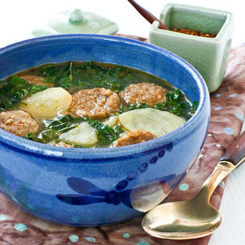 Caldo Verde (Portuguese Green Soup) with sausages, potatoes, and kale in an onion and garlic infused broth. It is a hearty and very flavorful soup. | RotiNRice.com