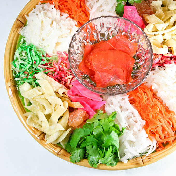 Yee Sang is a raw fish salad and a must-have for the Chinese New Year Feast. Make it at home using lox and a variety of crunchies and vegetables. | RotiNRice.com #yeesang #yusheng #prosperitytosssalad #chinesenewyear #lunarnewyear