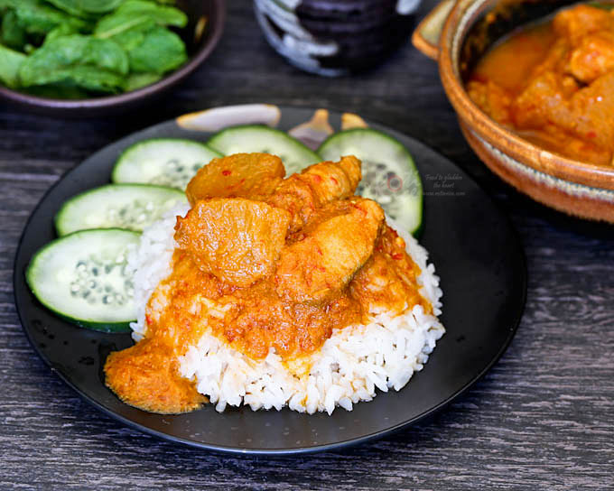 Spicy and tangy Pineapple Curry with Salmon served with rice and cucumbers.