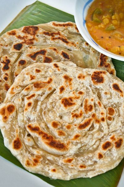 Crispy and fluffy homemade Roti Canai (Roti Paratha) with step-by-step instructions. Delicious eaten with dhal and chicken curry.   RotiNrice.com #roticanai #rotiparatha #rotipratha #indianflatbread