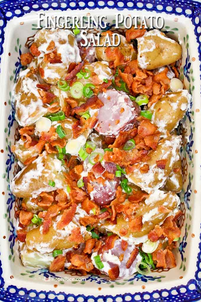Creamy fingerling potato salad topped with bacon bits and sliced green onions.