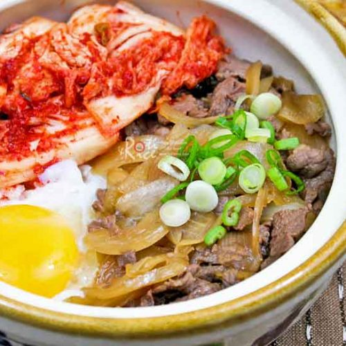 This flavorful Gyudon (Beef Bowl) topped with simmered beef, soft cooked egg, and cabbage kimchi makes a delicious and comforting meal.   RotiNRice.com