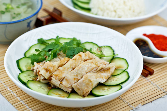 Homemade Hainanese Chicken Rice served with silky smooth poached chicken, thinly sliced cucumber, and garlic chili sauce. It is so simple yet so delicious. | RotiNRice.com
