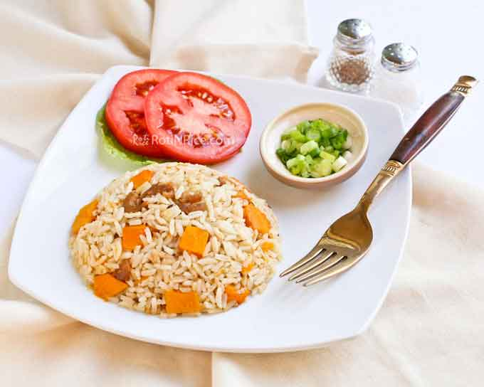 Inviting plate of spiced rice with slices of tomatoes, lettuce, and green onions.