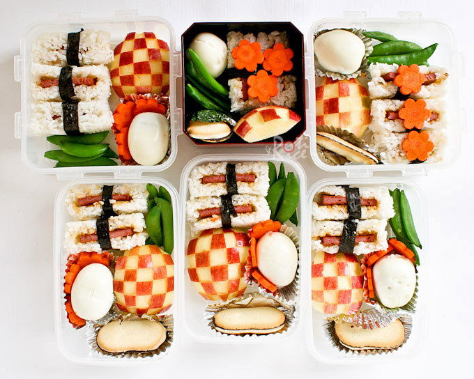 Bentos with Spam Musubi, molded eggs, and checker pattern apples.