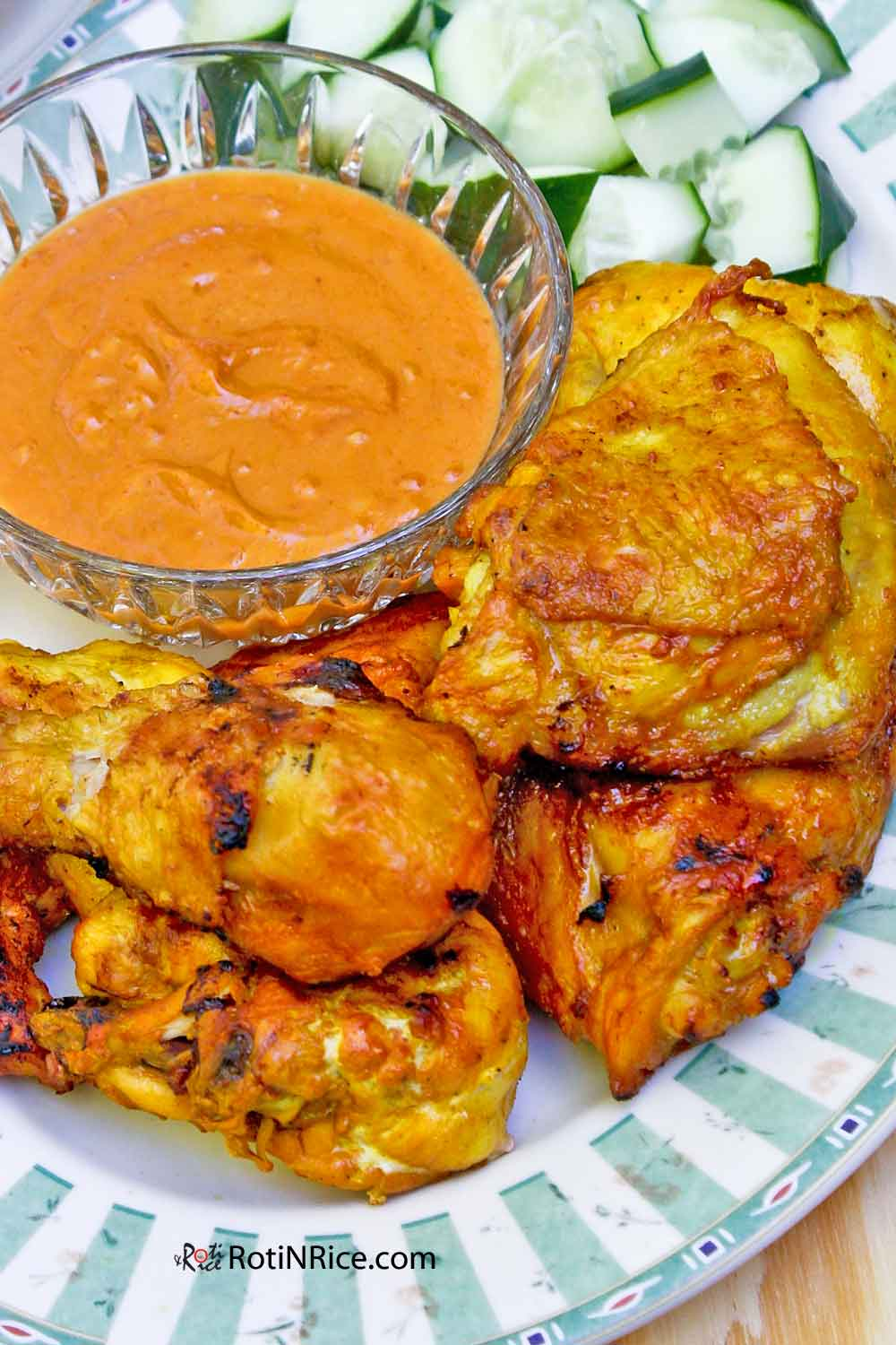 Ayam Panggang Kunyit made with ground turmeric served with spiced peanut sauce and cucumbers.