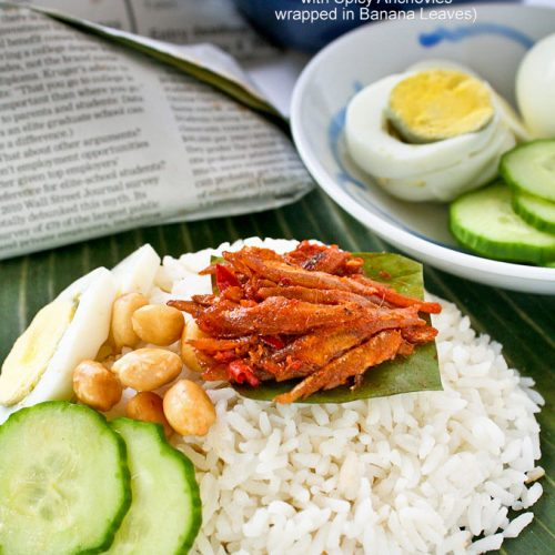 Nasi Lemak Bungkus topped with spicy anchovies, peanuts, hard boiled eggs, and cucumber slices.