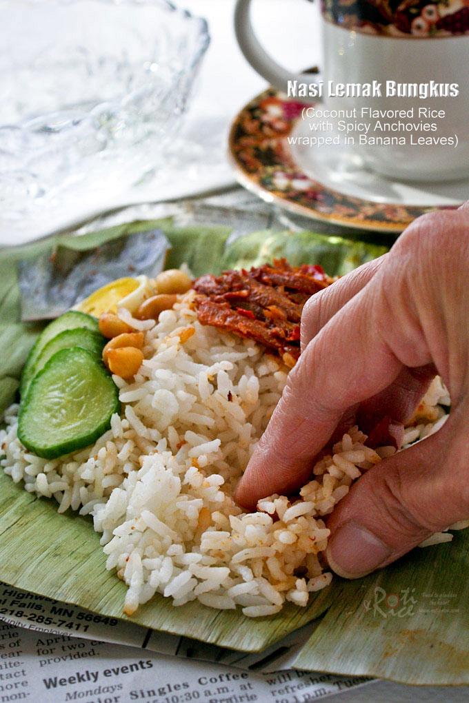 Eating Nasi Lemak Bungkus with fingers.