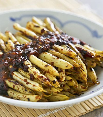 Tender crisp pan fried Szechuan Beans flavored with ginger, chili paste, and rice vinegar. This is a healthier alternative to the deep fried version. | RotiNRice.com