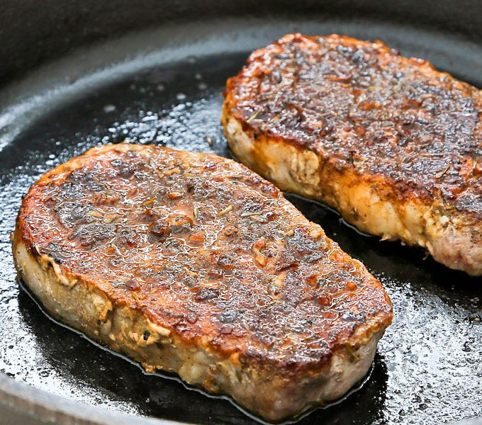 Pork Loin Chops being pan roasted in a cast iron skillet.