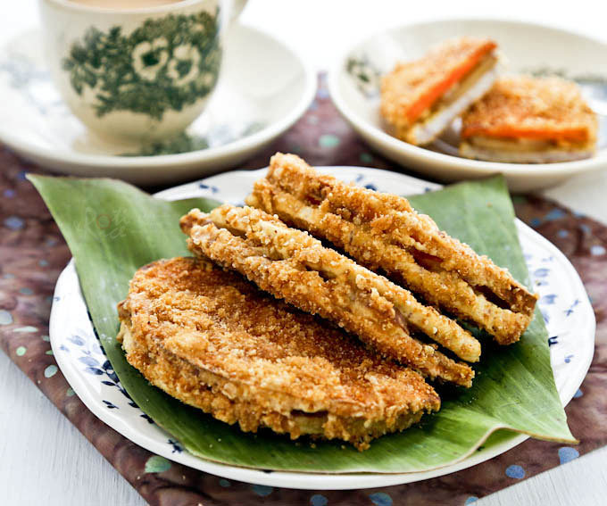 Crispy Yam Nian Gao Fritters on a plate lined with banana leaf served with a cup of tea.