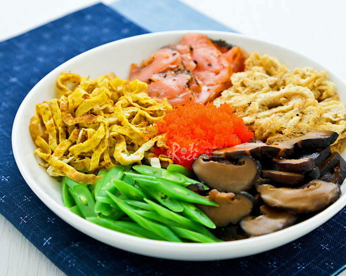 Easy and delicious Chirashi zushi topped with nori, shredded egg, tofu pockets, seasoned mushrooms, sliced green beans, lox, and fish roe. Very yummy! | RotiNRice.com