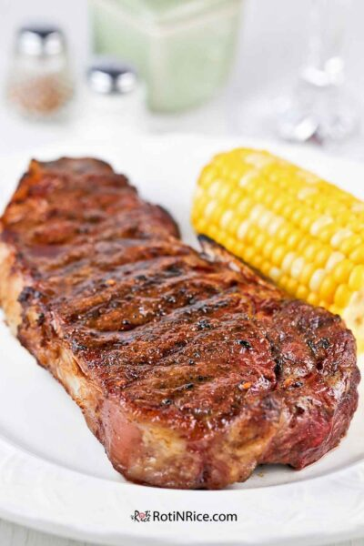 Grilled New York Strip Steaks served with corn-on-the-cob.
