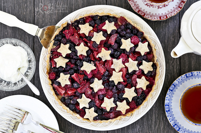 Delicious Triple Berry Tart with flaky hazelnut crust and juicy blueberries, strawberries, and raspberries filling. Recipe includes gluten free option. | RotiNRice.com