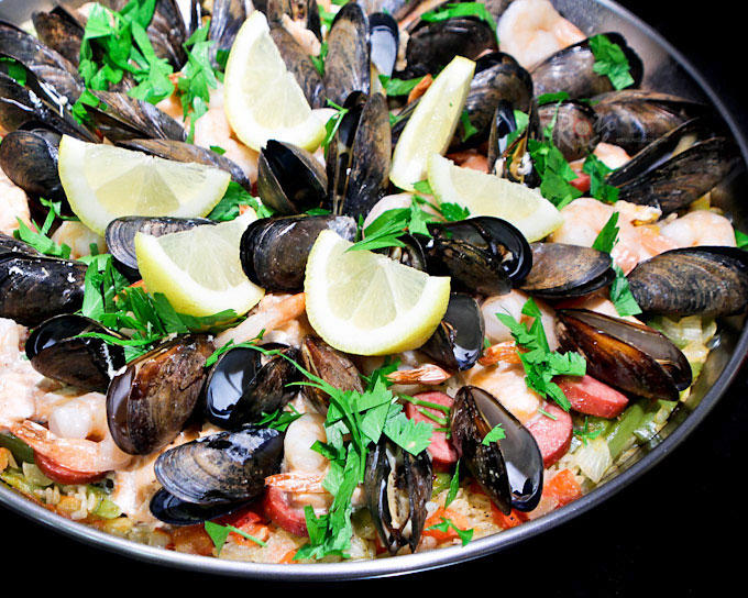 Fabulously tasty and attractive Seafood Paella with sausage, salmon, shrimp, and mussels. It is an experience you don't want to miss. | RotiNRice.com
