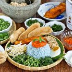 Nasi Kerabu Kelantan (Herb Rice) - a blue colored rice served with fresh herbs, salted egg, fish crackers, spiced sauce, and Crispy Skin Turmeric Salmon. | RotiNRice.com