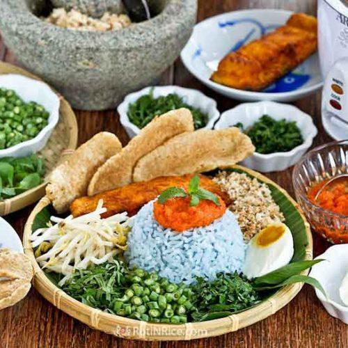 Nasi Kerabu Kelantan (Herb Rice) - a blue colored rice served with fresh herbs, salted egg, fish crackers, spiced sauce, and Crispy Skin Turmeric Salmon. | RotiNRice.com