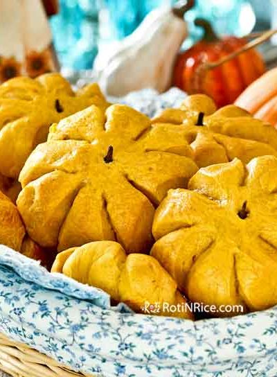 These golden Pumpkin Dinner Rolls are fun and festive. They are soft and have a lovely hint of pumpkin and spices, perfect for any time of the year. | RotiNRice.com #pumpkinrolls #dinnerrolls #thanksgiving #christmas #holidayrolls