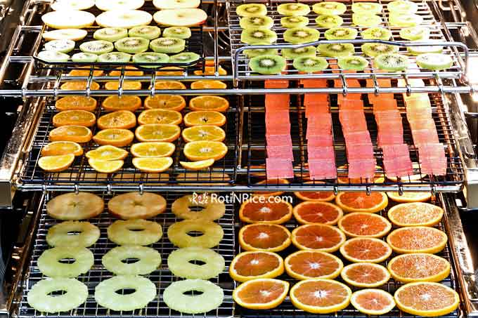 Racks of apples, kiwi fruits, clementines, pineapple, and cara cara oranges in the oven ready for drying.