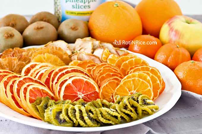 A plate of dried fruits made from 1 can of pineapple slices, 1 honey crisp apple, 4 clementines, 5 kiwi fruits, and 2 cara cara oranges.