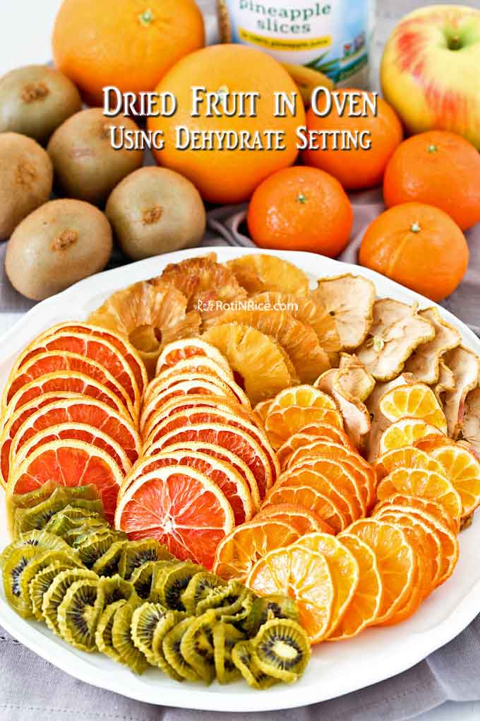 A plate full of colorful dried pineapple, apple, clementines, kiwi fruit, and cara cara oranges.