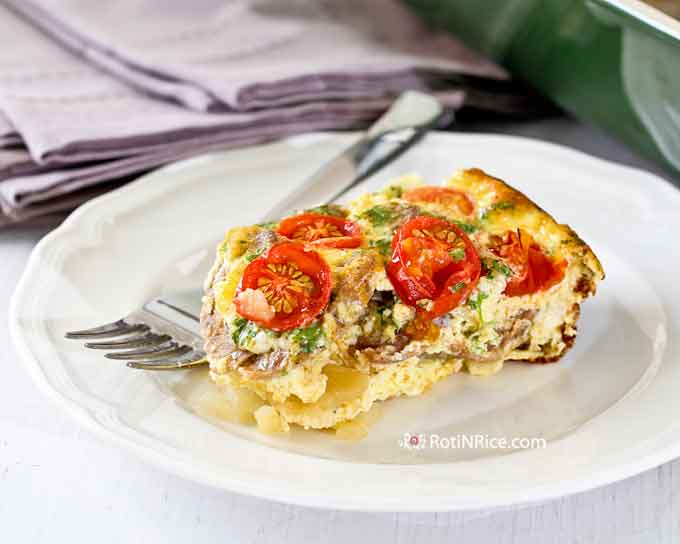 A slice of delicious Egg Bake with layers of potatoes, sausage, and tomatoes.