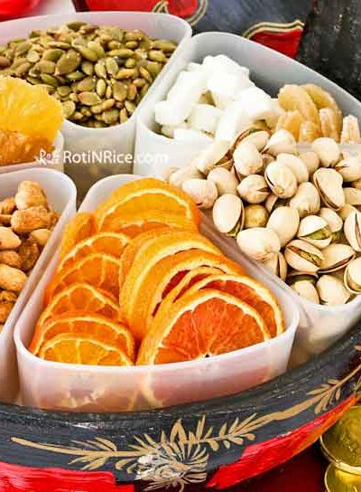 Putting together a Tray of Togetherness (Chinese New Year Candy Box) with dehydrated fruits, melon seeds, and nuts which hold symbolic meanings. | RotiNRice.com #trayoftogetherness #chinesenewyearcandybox #chinesenewyear #lunarnewyear