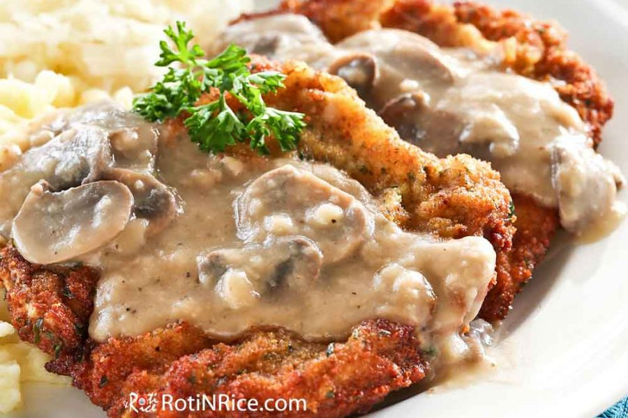 A closeup of the Jagerschnitzel topped with Creamy Mushroom Sauce served with spaetzle and sauerkraut.