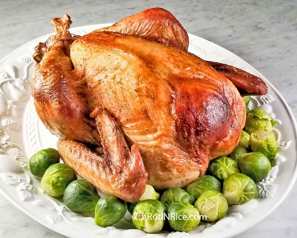 Perfectly roasted Make Ahead Roast Turkey surrounded by steamed brussel sprouts.