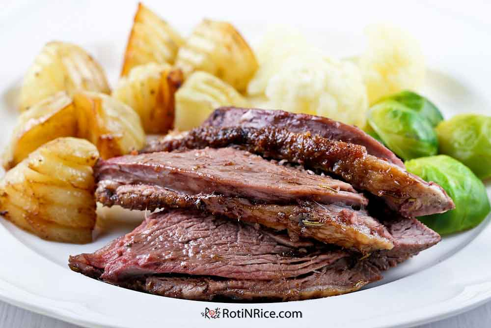A delicious dinner of Roast Lamb and potatoes with brussel sprouts.
